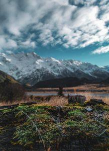 Tiroler Bergpanorama mit Schnee hinter einem grünen Hügel mit Wolken